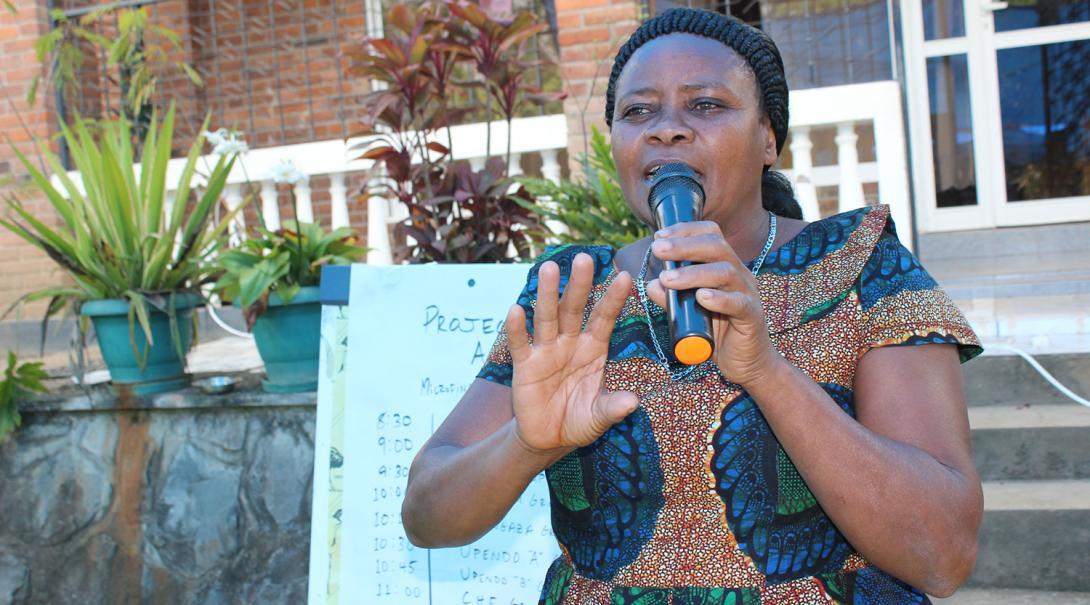 Mujer tanzana dando un discurso sobre empoderamiento de la mujer.